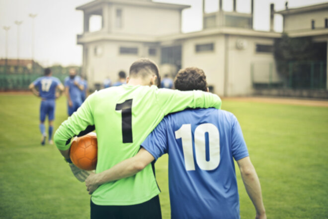 Two soccer players on a soccer field with uniforms walking with their arms around each other