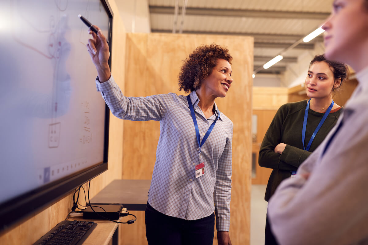 Woman gesturing towards a smart board with a marker in front of group of people